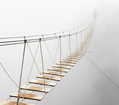 Rope bridge leading into mist