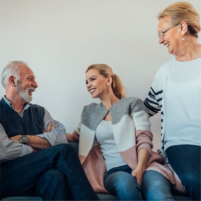 Blond daughter in grey, white and pink sweater seated between father with grey beard and blond mother, all smiling at each other.