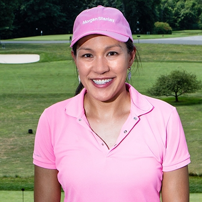 Woman in pink polo shirt and pink Morgan Stanley baseball cap smiling with golf course in background.