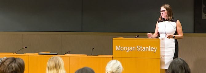 Business woman at Morgan Stanley podium presenting to an audience with a white and black dress and glasses.