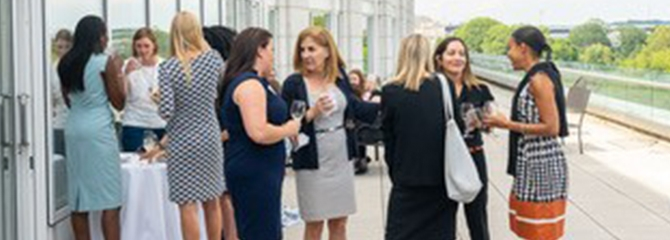 Group of business women gathered at a reception outside on a patio, speaking with one another.